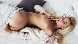 women, blonde, tanned, in bed, ass, ribs, boobs, finger on lips, pants, jeans, top view, sweater