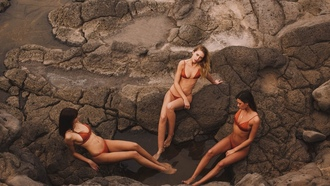 women, red bikinis, tanned, water, sitting, necklace, top view, rocks, women outdoors, belly, group of women