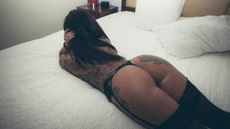 women, ass, tanned, black stockings, lying on front, tattoo, pillowin bed, garter belt, painted nails