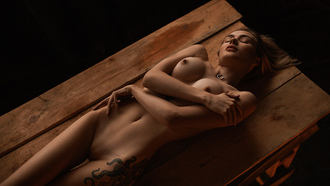women, nude, tattoo, table, arms crossed, lying on back, boobs, nipples, belly, shaved pubic hair, skinny, piercing nipples, closed eyes, brunette