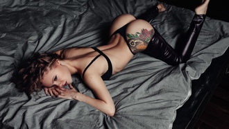 women, bottom up, brunette, in bed, ass, tattoo, leather leggings, black lingerie, arched back, eyeliner, venus dimples, painted nails, undressing