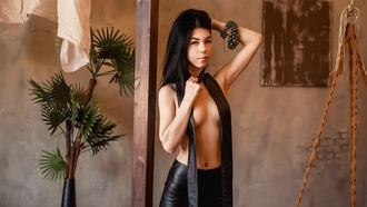 women, topless, portrait, bed, leather leggings, plants, boobs, strategic covering, black hair, belly, wall, eyeliner